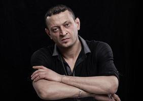 portrait d'homme fronçant les sourcils sur fond noir photo