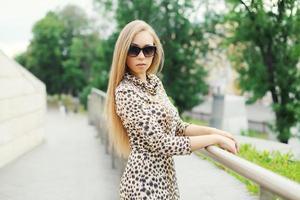 Belle jeune femme blonde vêtue d'une robe léopard et sunglas