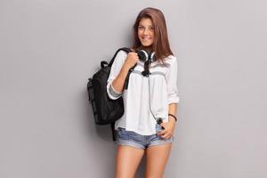 Écolière adolescente avec des écouteurs portant un sac à dos photo
