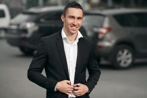 homme souriant réussi dans un costume noir, dans la rue photo