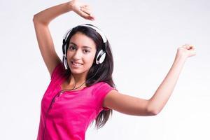Studio isolé tourné belle jeune femme joyeuse dansant sur la musique photo
