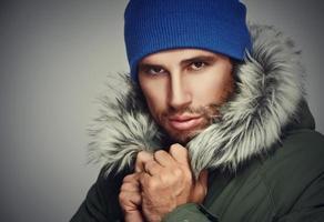 visage brutal, un homme aux poils de barbe et à capuche en hiver photo