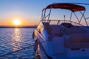 yacht près de la jetée contre le coucher du soleil