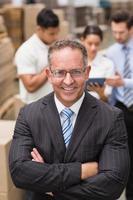 patron portant des lunettes debout avec les bras croisés photo