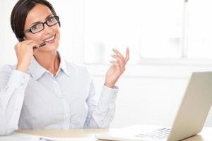 réceptionniste fille latine conversant sur son écouteur photo