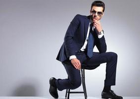 jeune homme d'affaires assis sur un tabouret