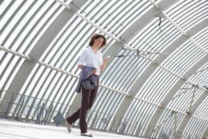femme affaires, marche, et, regarder téléphone portable photo