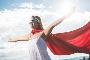 jeune femme posant comme super-héros sur ciel bleu