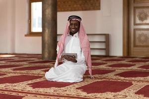 Bel homme du Moyen-Orient à l'aide d'un pavé tactile photo