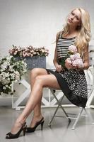 femme assise dans la chaise, tenant un bouquet de pivoines photo