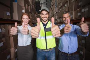 équipe d'entrepôt souriant à la caméra montrant les pouces vers le haut photo