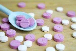 groupe de médicaments sur une cuillère et une planche de bois photo