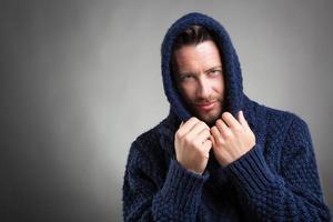 Homme barbu à capuche portant un pull bleu