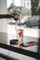 personne versant du thé dans un verre transparent photo
