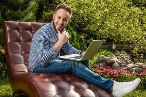 jeune bel homme assis dans un canapé de luxe avec ordinateur portable. photo