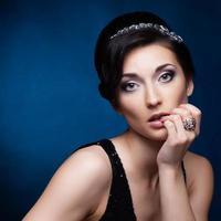 portrait de la belle femme brune en robe noire. cosmétique