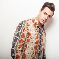 élégant jeune bel homme en chemise colorée lumineuse.