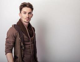 séduisant jeune homme dans un pull marron pose en studio. photo