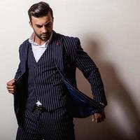 élégant jeune bel homme en costume bleu foncé classique.