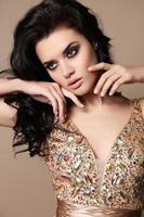 femme sensuelle aux cheveux noirs avec bijou en robe luxueuse