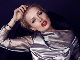 Femme aux cheveux blonds portant une robe argentée luxueuse photo