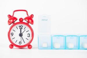 boîte à pilules hebdomadaire et horloge rouge montrent l'heure du médicament photo