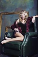 Jeune femme blonde portant la couronne dans l'intérieur de luxe de fée avec photo