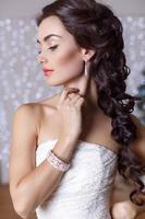 belle mariée élégante aux cheveux noirs posant au studio photo