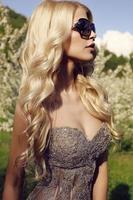 Fille blonde sensuelle en robe à paillettes luxueuse avec des lunettes de soleil