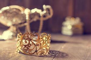 bracelet doré et vase en argent avec des bijoux sur fond de bois