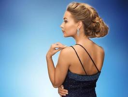 belle femme avec boucle d'oreille diamant sur bleu photo