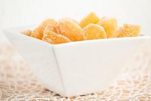Bonbons au gingembre dans un bol en porcelaine blanche photo