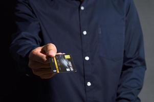 personne tenant une carte de crédit