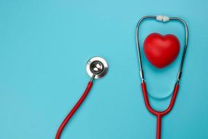 Mise à plat d'un stéthoscope et coeur sur fond bleu