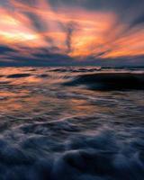 vagues de l'océan sous un ciel coloré au coucher du soleil photo