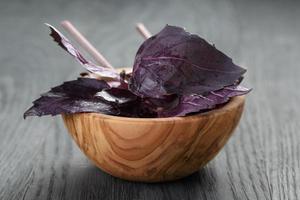 Feuilles de basilic vert et violet dans un bol en bois sur la table photo