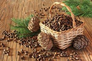 Les noix de cèdre dans le panier en osier sur une table en bois photo