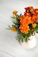 Fleurs de souci dans un vase sur fond gris