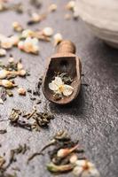 Thé au jasmin dans une cuillère en bois foncé, gros plan