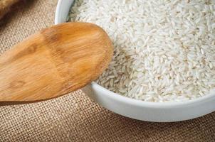 Céréales de riz et cuillère en bois sur fond de toile de jute photo