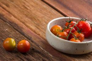 tomates cerises fraîches sur fond de bois ancien photo