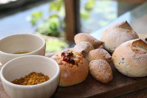 Assortiment de petits pains artisanaux sur une planche de bois photo