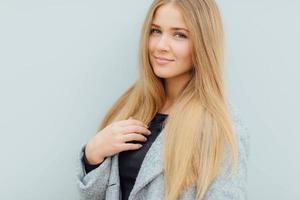 femme cheveux blonds marchant dans la rue et sourire photo