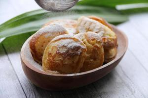 Poffertjes dans un bol en bois ovale saupoudré de sucre en poudre