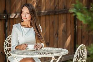 portrait en plein air de la belle jeune fille en robe blanche de luxe.