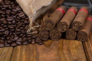 Cigares cubains et grains de café rouille sur bois photo