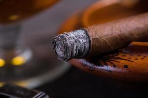 Fermer la vue sur le cigare cubain avec de la cendre photo