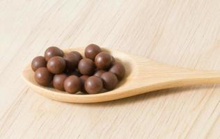 Pastilles contre la toux à base de plantes sur une cuillère en bois brun photo