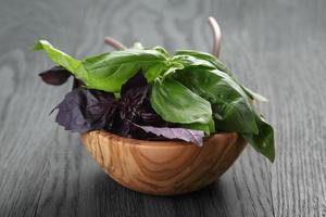 Feuilles de basilic vert et violet dans un bol en bois sur la table