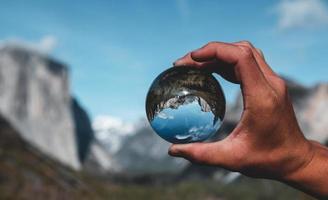 main tenant une boule de verre dans le parc national de yosemite photo